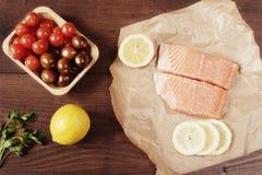 Rå lax på bakningpapper, körsbärsröda tomater, citronen och persilja arkivbild