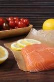 Rå lax på bakningpapper, körsbärsröda tomater, citronen och persilja royaltyfria foton