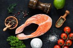 Rå laxbiff, grönsaker och kryddor för att laga mat på svart kritiserar arkivfoton
