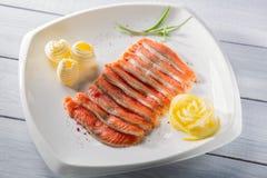 Rå laxfiléstycken tjänade som med kryddor, citronen, smör och örter på den vita plattan och trätabellen royaltyfria foton