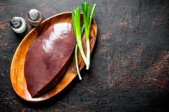 Rå lever på en platta av salladslökar och kryddor royaltyfri foto
