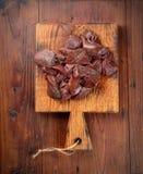 Rå leverskivor på en skärbräda på en träbakgrund royaltyfria foton