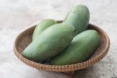 Rå mango på korg Fotografering för Bildbyråer