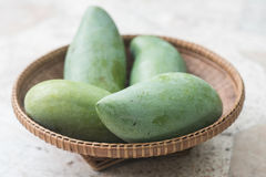 Rå mango på korg Royaltyfri Foto