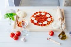 Rå margheritapizza på träbakelsebräde Royaltyfri Bild