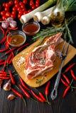 rå meatpork Nya biffar kritiserar på brädet på svart bakgrund royaltyfri bild