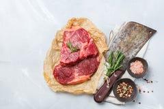 Rå nötköttbiff med kryddor som är klara för att laga mat matställen Royaltyfria Bilder