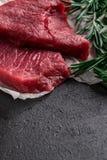 Rå nötköttbiff med nya filialrosmarin på svart bakgrund royaltyfri foto