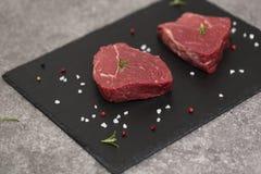 Rå nötköttbiff och kryddor kritiserar på brädet Rått kött på svart bakgrund royaltyfria bilder