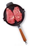 Rå nötköttbiff på stekpannan som är klar att laga mat, isolerat på vit Arkivbilder