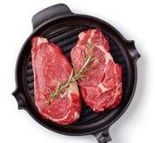 Rå nötköttbiff på stekpannan som är klar att laga mat, isolerat på vit Fotografering för Bildbyråer