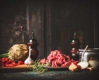 Rå nötköttgulasch med grönsaker och matlagningingredienser på det mörka lantliga köksbordet fotografering för bildbyråer