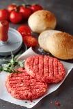 Rå nötkötthamburgaresmå pastejer med press och Rolls Royaltyfri Bild
