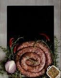 Rå nötköttkorvar på en järn- panna, selektiv fokus Arkivbild