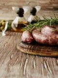 Rå nötköttkorvar på en järn- panna, selektiv fokus arkivbilder