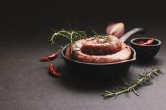 Rå nötköttkorvar på en järn- panna, selektiv fokus royaltyfria foton