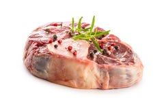 Rå nötköttlägg med salt peppar och rosmarin som isoleras på vit b Arkivfoton