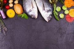 Rå ny doradofisk med brussels groddar, tomater, citronen, den unga potatisen och gräsplaner Royaltyfri Foto