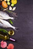 Rå ny doradofisk med brussels groddar, tomater, citronen, den unga potatisen och gräsplaner Royaltyfria Bilder