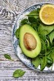 Rå nya behandla som ett barn spenat och klipper avokadot med citronskivan Arkivbild