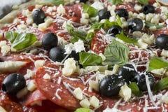 Rå okokt pizza med peperonisalami, svarta oliv, basilika och ost royaltyfri bild
