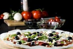 Rå okokt pizza med peperonisalami, svarta oliv, basilika och ost arkivbild