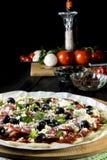 Rå okokt pizza med peperonisalami, svarta oliv, basilika och ost arkivfoto