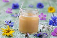 Rå organisk kunglig gelé i en liten flaska med litteskeden på den lilla flaskan som omges av blommor Royaltyfri Fotografi