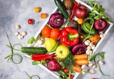 Rå organiska grönsaker med nya ingredienser för healthily att laga mat i det vita magasinet på konkret bakgrund arkivfoton