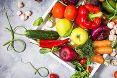 Rå organiska grönsaker med nya ingredienser för healthily att laga mat i det vita magasinet på konkret bakgrund royaltyfri foto