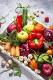 Rå organiska grönsaker med nya ingredienser för healthily att laga mat i det vita magasinet på konkret bakgrund arkivbild