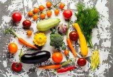 Rå organiska grönsaker med nya ingredienser för healthily att laga mat på konkret bakgrund, bästa sikt, baner Strikt vegetarian e Royaltyfri Foto