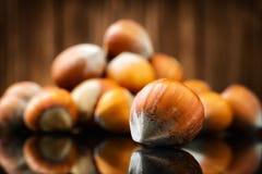 Rå organiska hela hasselnötter på träbakgrund Royaltyfria Bilder