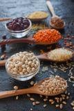 Rå organiska sädes- korn, frö och bönor i träskedar och bunkar arkivbilder