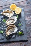 Rå ostron på det svarta stenbrädet royaltyfri fotografi
