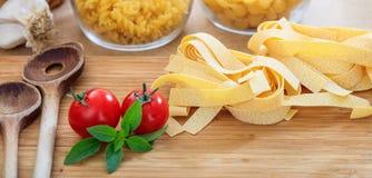 Rå pappardellepasta med tomater och vitlök Arkivfoto