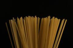 Rå pasta för italiensk spagetti, mörk bakgrund royaltyfria foton