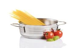 Rå pasta i den metalliska krukan som isoleras på vit bakgrund Royaltyfri Bild
