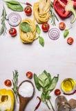 Rå pasta med färgrikt olikt av den organiska lantgårdgrönsaken, det träsked-, smör- och örtstället för text, ram på trälantliga l Royaltyfri Bild