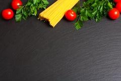 Rå pasta med tomater och persilja Royaltyfria Bilder