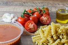 Rå pasta och ingredienser ( nudel körsbärsröda tomater, olivolja, garlic) för gör traditionell italiensk mat arkivbilder