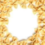 Rå pasta på vit inramar bakgrund Arkivbild