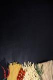 Rå pasta, tomater, rosmarin, chilipeppar på den svarta trätabellen Utrymme för text, sikt för hög vinkel Royaltyfri Bild