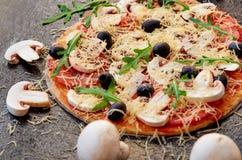 Rå pizza på det svarta bakgrundsslutet som dekoreras upp med vita champinjoner Vegetarisk pizza med ost, grönsaker, svarta oliv Royaltyfri Bild