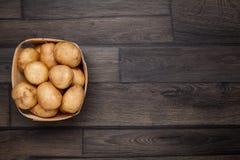 Rå potatis och korg på royaltyfri bild