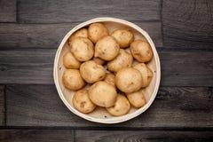 Rå potatis och korg på arkivfoton