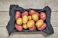 Rå potatis på den svarta wood tabellen i kök Preperation för att laga mat arkivfoton