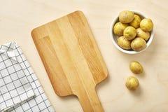 Rå potatis på tabellen med skärbräda- och textilservetten arkivbilder