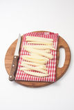 Rå potatisar för pommes frites och en träkökkniv Royaltyfria Bilder