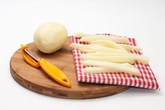 Rå potatisar för pommes frites och ett hjälpmedel för att skala Royaltyfri Bild